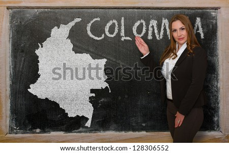 Successful, beautiful and confident young woman showing map of colombia on blackboard for presentation, marketing research and tourist advertising - stock photo