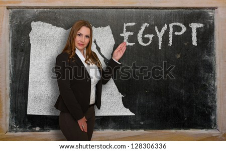 Successful, beautiful and confident young woman showing map of egypt on blackboard for presentation, marketing research and tourist advertising - stock photo