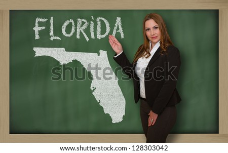 Successful, beautiful and confident young woman showing map of florida on blackboard for presentation, marketing research and tourist advertising - stock photo