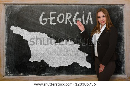Successful, beautiful and confident young woman showing map of georgia (2) on blackboard for presentation, marketing research and tourist advertising - stock photo
