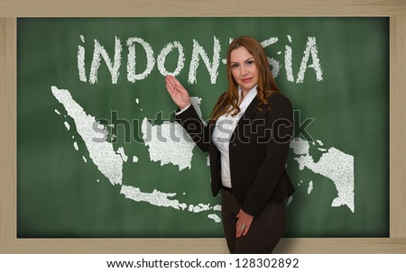 Successful, beautiful and confident young woman showing map of indonesia on blackboard for presentation, marketing research and tourist advertising - stock photo