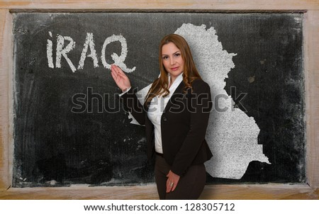 Successful, beautiful and confident young woman showing map of iraq on blackboard for presentation, marketing research and tourist advertising - stock photo