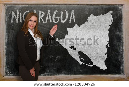 Successful, beautiful and confident young woman showing map of nicaragua on blackboard for presentation, marketing research and tourist advertising - stock photo