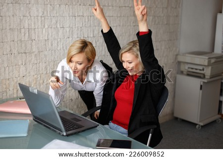 Successful blonde young managers in office with laptop
