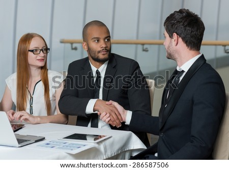 Successful business agreement. Team of  confident and motivated business professionals are working on the project. Men in formal suits are shaking hands Office business concept - stock photo