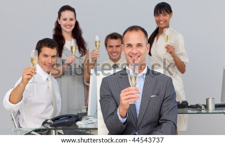 Successful business co-workers toasting with Champagne in the office