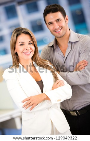 Successful business couple at the office looking confident - stock photo