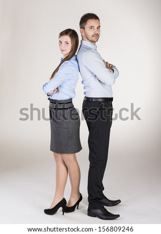 Successful business couple is standing in studio - stock photo