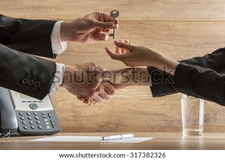 Successful business deal - real estate agent and new female homeowner exchanging house key while shaking hands over a contract of house sale. - stock photo
