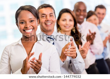 Successful business group applauding at the office - stock photo