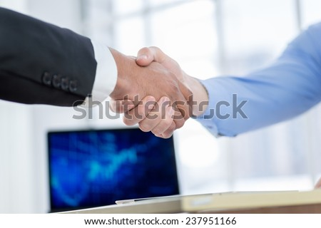 Successful business handshake. Close-up view of a handshake while two successful businessman shaking hands at the table against each in the business office in formal wear and work at a laptop. - stock photo