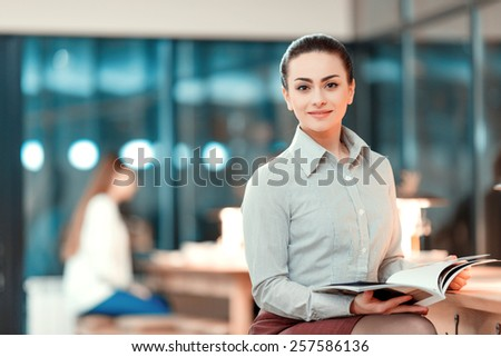 Successful business lady. Beautiful young woman in formalwear holding a corporate magazine and smiling while leaning at bar counter - stock photo