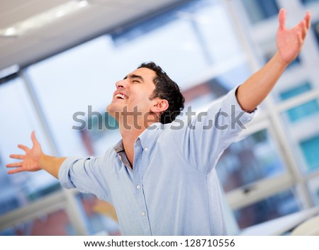 Successful business man celebrating with arms open