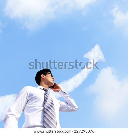 Successful Business man concept -  business man talking on smart phone with growth arrow cloud in sky - stock photo