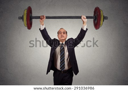 Successful business man effortlessly lifting heavy barbell isolated on gray wall background. Determination task completion hard work concept   - stock photo