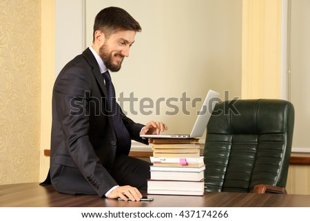 successful business man sitting at office table and working with laptop