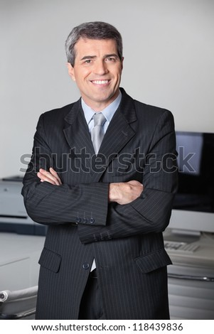 Successful business man smiling with his arms crossed - stock photo