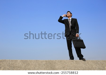 Successful business man speak phone with blue sky, asian male - stock photo