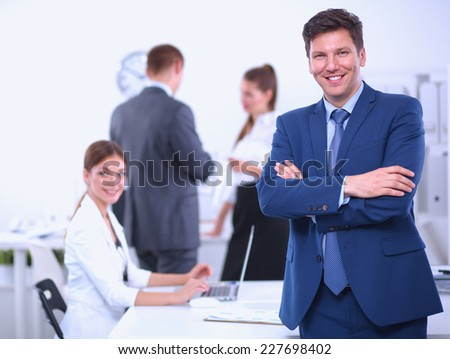 Successful business man standing with his staff in  office - stock photo