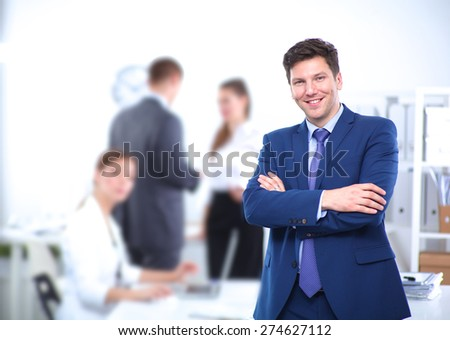 Successful business man standing with his staff in office. - stock photo