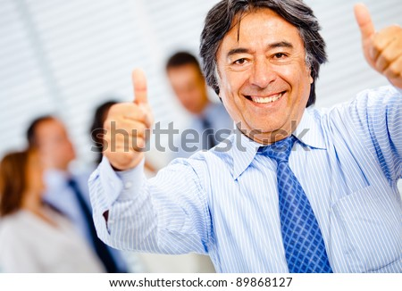 Successful business man with thumbs-up at the office - stock photo