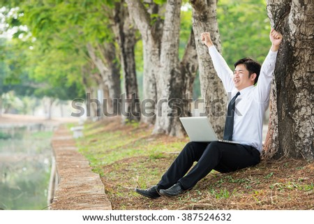 Successful Business man working outdoor with a laptop (Focus on the man) - stock photo
