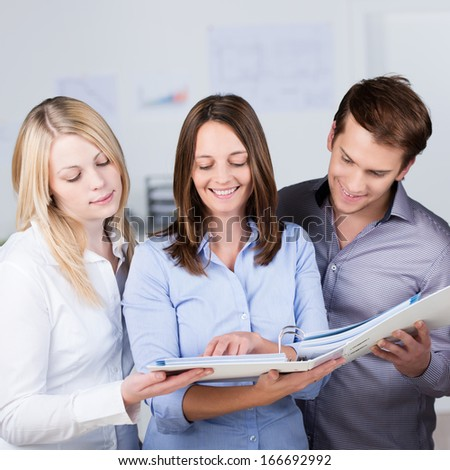 Successful business partners consulting a file together held by the woman in the centre smiling happily as they see their project in print - stock photo