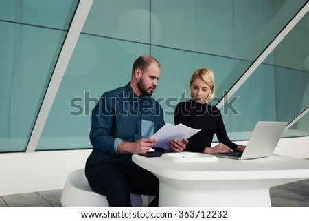 Successful business people checks monthly income on paper documents and laptop computer while sitting in office space, man and woman professional bookkeepers working together with reports and net-book - stock photo