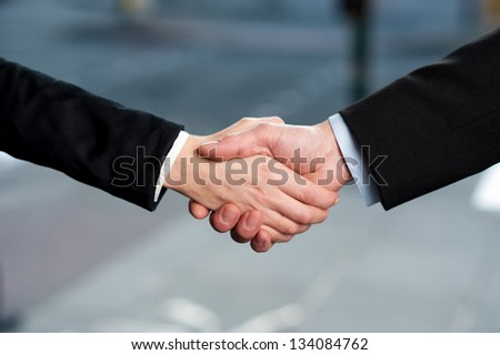 Successful business people shaking hands after closing a deal.