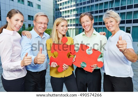 Successful business people with big red jugsaw puzzle pieces holding thumbs up