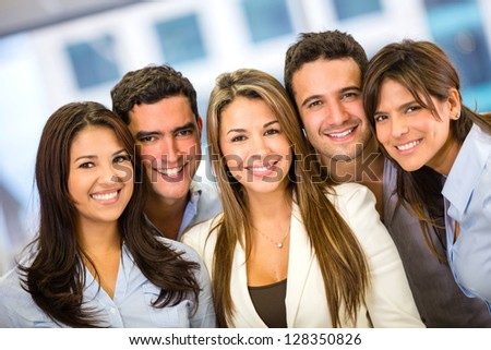 Successful business team at the office looking happy - stock photo