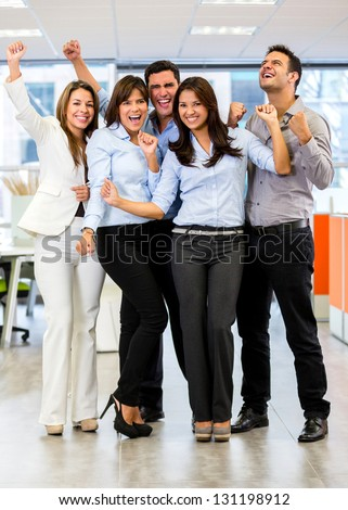 Successful business team at the office with arms up - stock photo