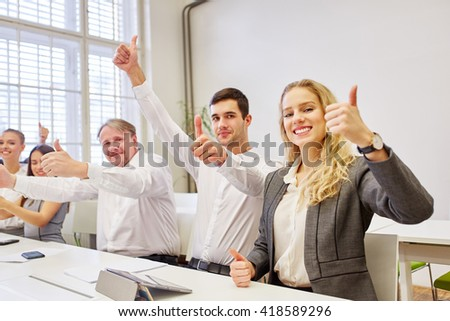 Successful business team cheering with thumbs up their success