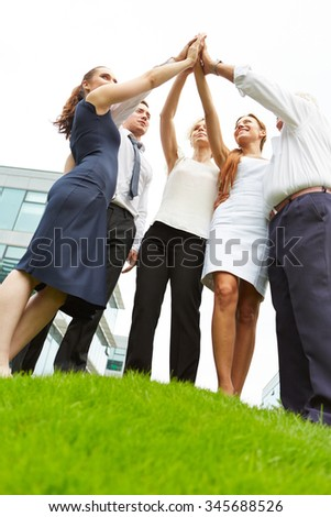 Successful business team doing high five for motivation - stock photo