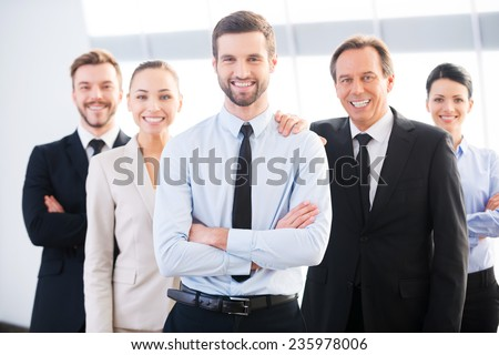 Successful business team. Group of confident business people in formal wear standing close to each other and smiling  - stock photo