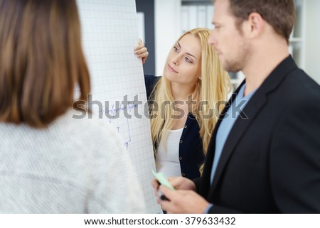 Successful business team in a brainstorming meeting standing around a flip chart having a discussion with serious expressions, focus to a young lady - stock photo
