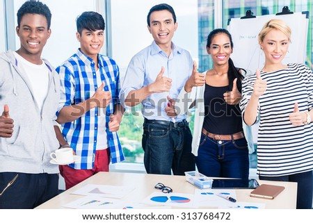 Successful business team in kickoff meeting with flipchart and graphs on the table, international diversity setting - stock photo