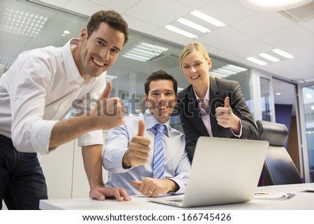 Successful business team in office, giving thumbs up, looking camera - stock photo