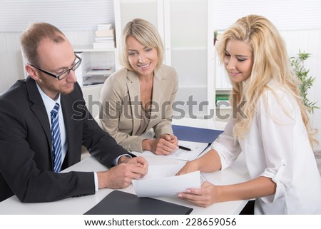 Successful business team of man an woman sitting around a table talking together. - stock photo