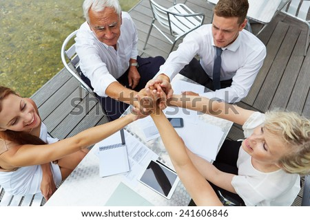Successful business team on a table holding their hands for motivation