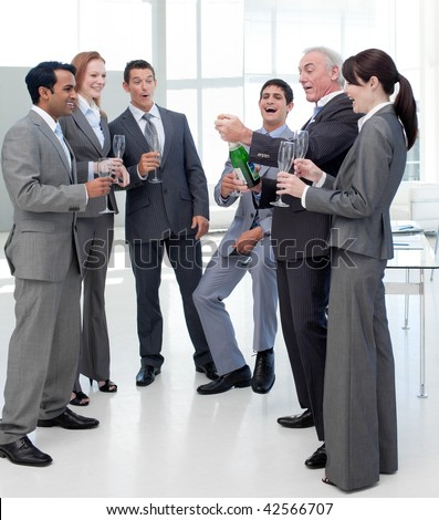 Successful business team popping the cork on a bottle of Champagne in the office - stock photo