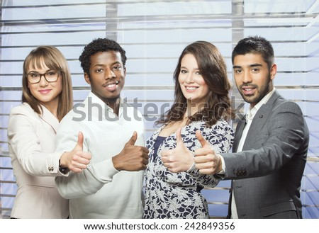 Successful business team showing thumbs up in the office - stock photo