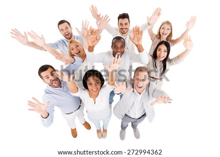 Successful business team. Top view of positive diverse group of people in smart casual wear looking at camera and stretching out their hands while standing close to each other - stock photo