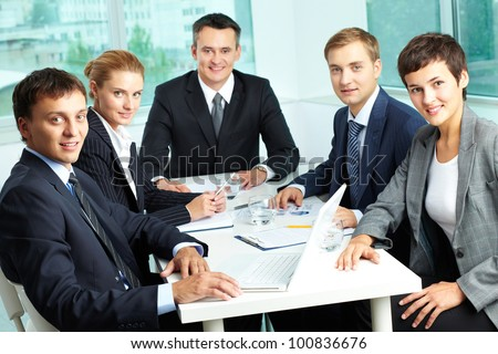 Successful business team with an experienced leader at the head looking at camera
