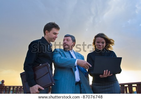 Successful business team working on laptop and striking a bargain(deal). Internet business through wireless technology