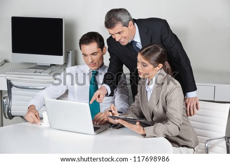 Successful business team working on laptop computer in the office - stock photo