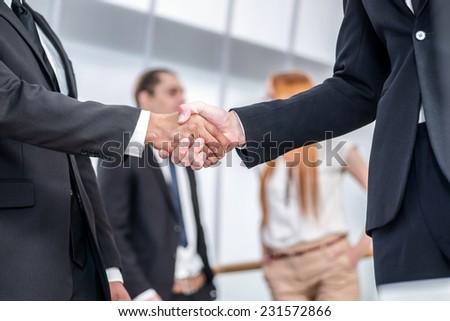 Successful business. Two Confident businessman firmly shake hands with each other while two colleagues talking in the background - stock photo