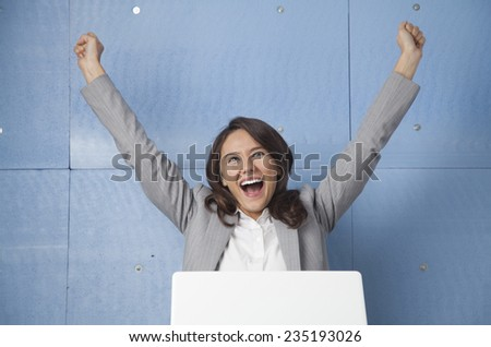 Successful business woman celebrating with arms up - stock photo