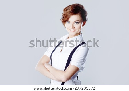 Successful business woman, in shirt on white background, pants with suspenders - stock photo