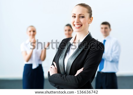 successful business woman in the office. against colleagues - stock photo